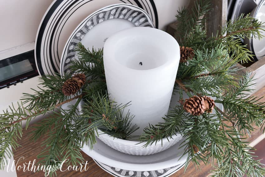 Chunky white candle surrounded with artificial greenery for winter || Worthing Court