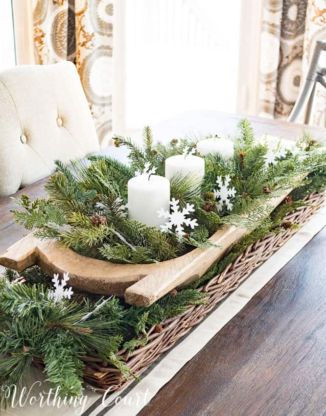 Super easy and fast winter centerpiece in a dough bowl with candles and evergreen on the coffee table.