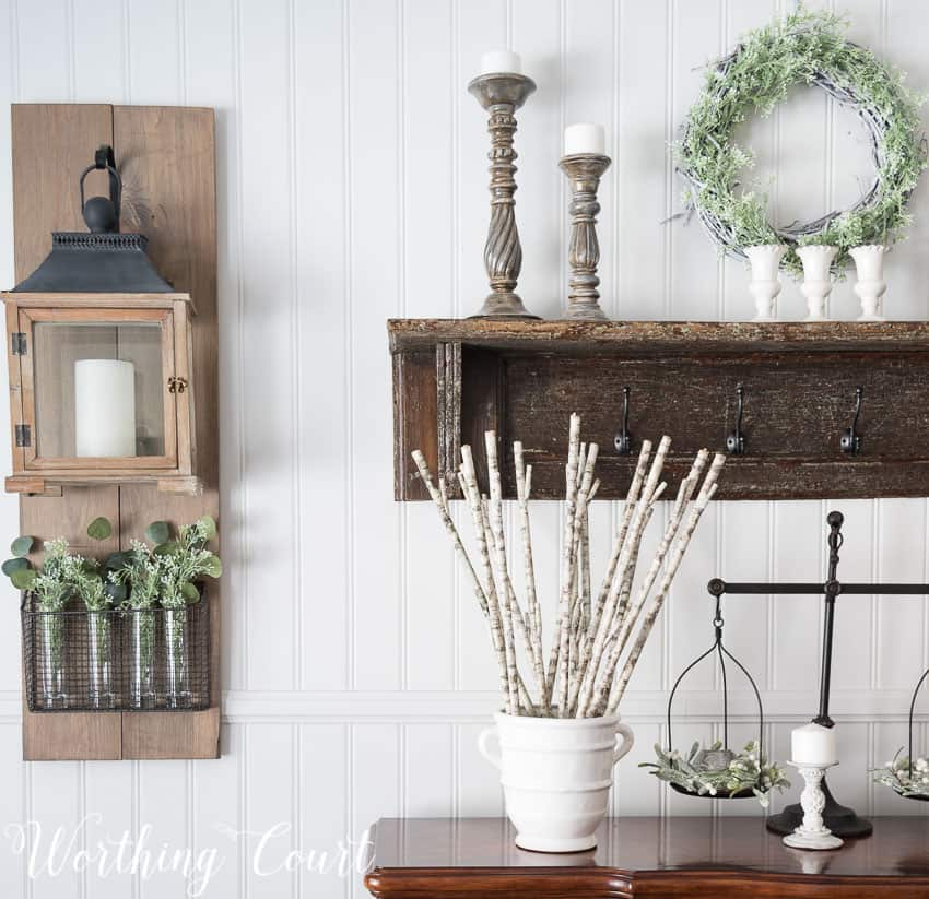 Winter farmhouse dining room decor with candles decorating the sideboard and a wooden shelf with candlesticks on it.