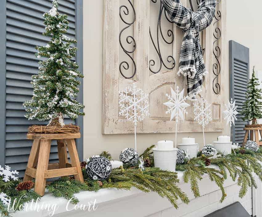 Winter mantel decorated with faux greenery, white candles and diy snowflakes on a stick