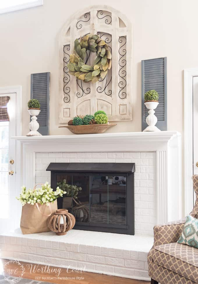 Farmhouse style white painted brick fireplace and mantel decorated for spring || Worthing Court