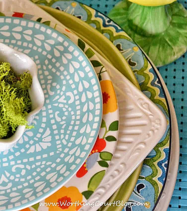 multiple colors of dishes stacked together for a spring tablescape