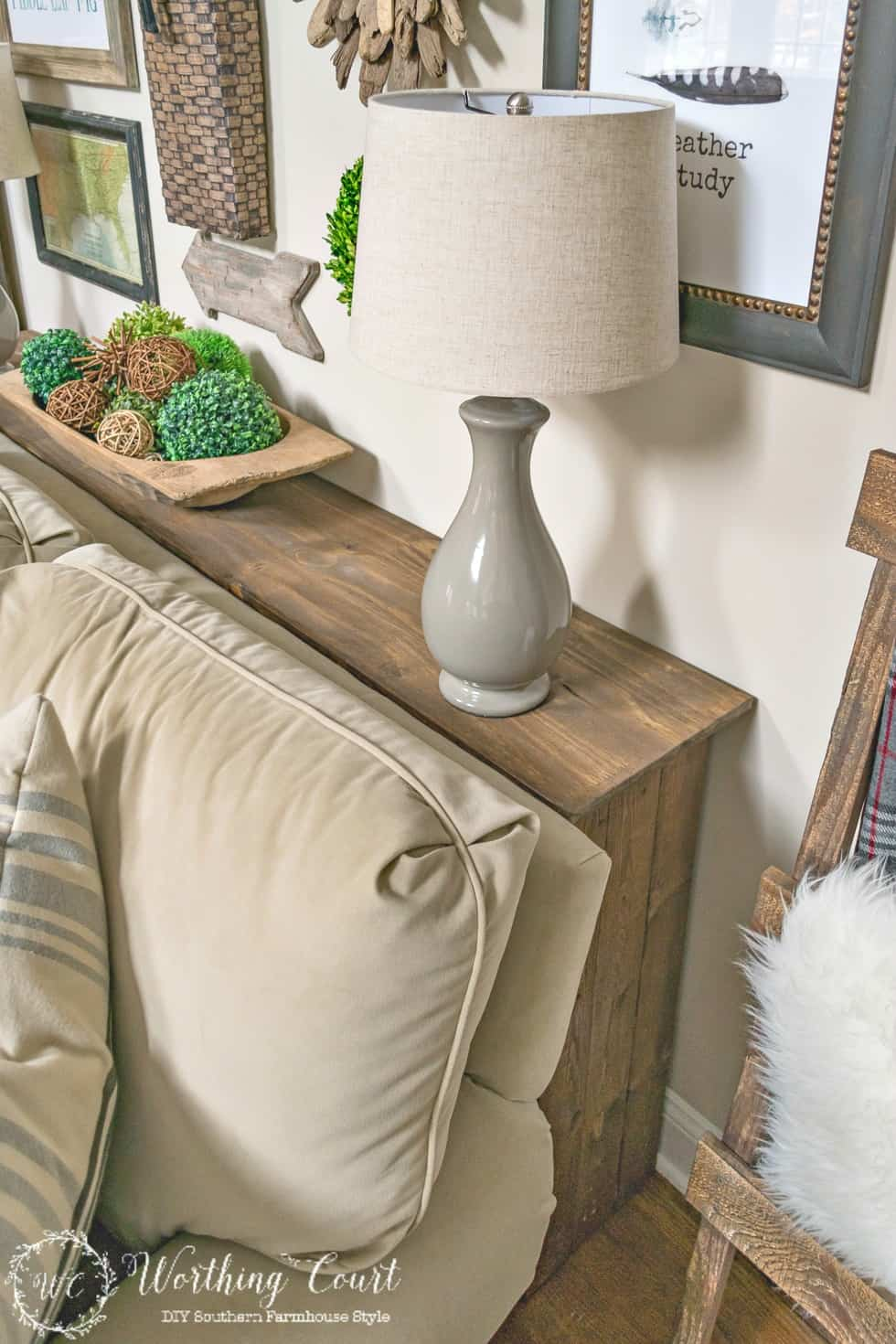 A wooden farmhouse sofa table behind the neutral sofa, with a small lamp on top.