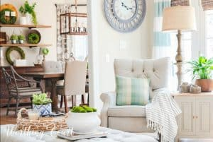 neutral accent chair with pillow and throw