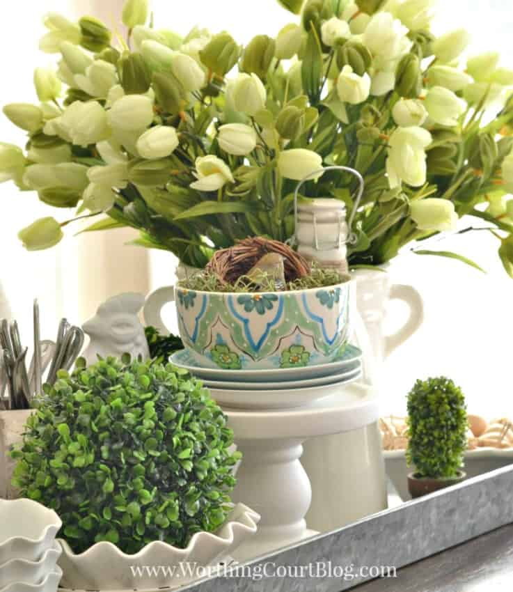Spring centerpiece with white tulips and greenery around it.