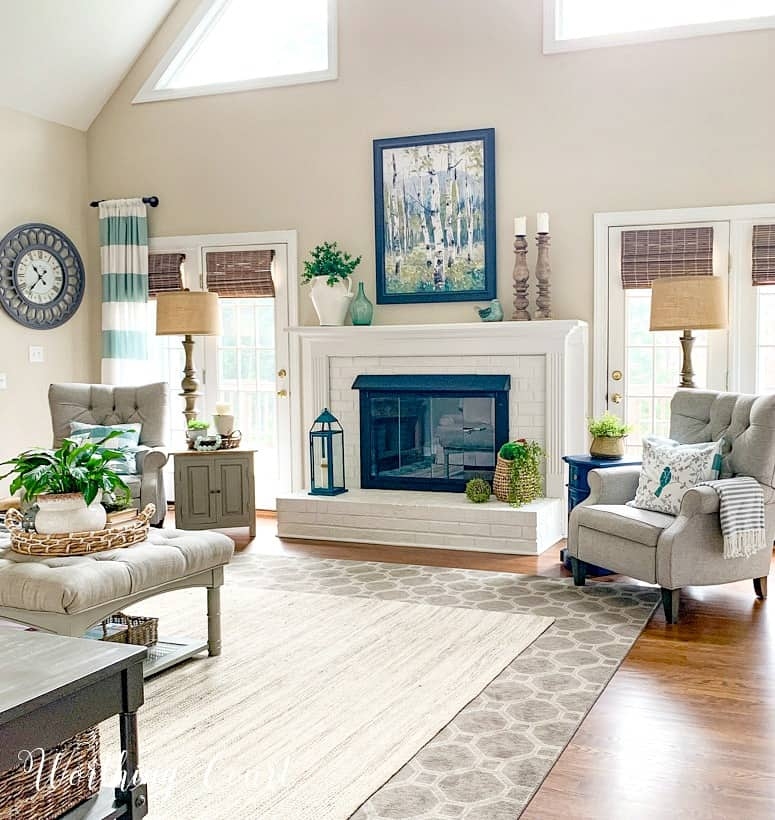 family room with white brick fireplace flanked by gray recliners