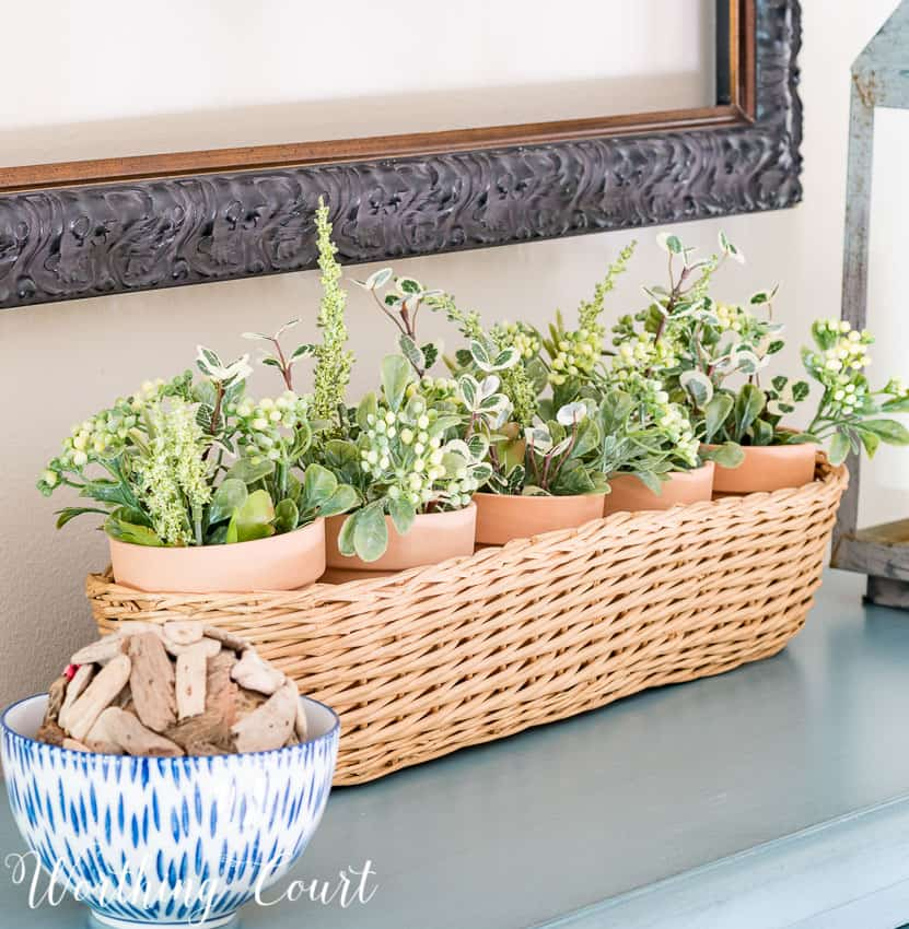 Clay pots from the dollar store placed in a thrifted basket and filled with clippings from artificial greenery bushes || Worthing Court