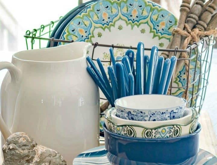 centerpiece with blue white and green dishes on a breadboard