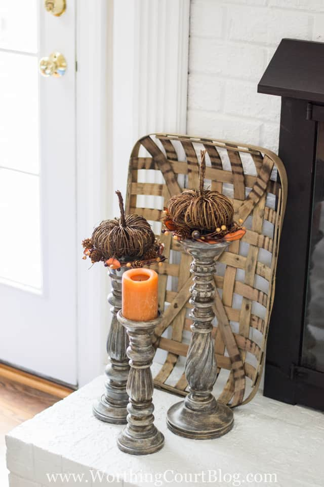 gray candlesticks on hearth with fall decorations
