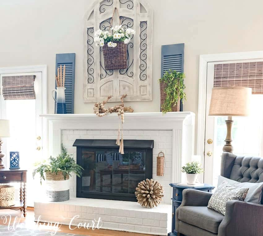 Painted red brick fireplace decorated for summer with simple organic elements || Worthing Court