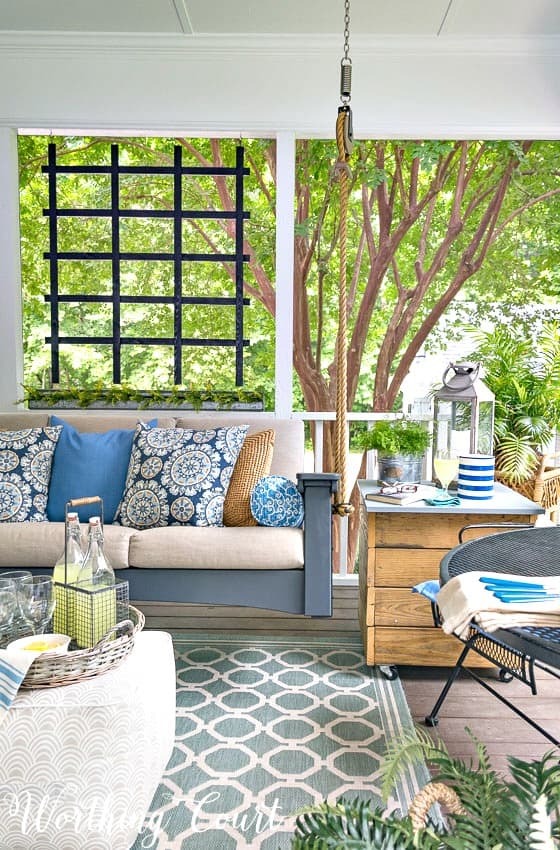 How To Make A Screened In Porch A Relaxing Oasis. A screened in porch turned into an oasis with the addition of a swinging sofa and pretty accessories. #screenporchdecorating #screenporchideas #screenporchdesign #screenporchrug #screenporchfurnture #screenporchmakeover #screenporchonabudget #swingingbedideas #outdoorrug
