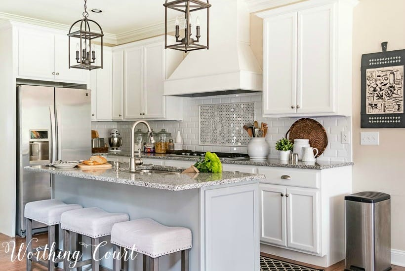 kitchen with white shaker cabinets and a gray island