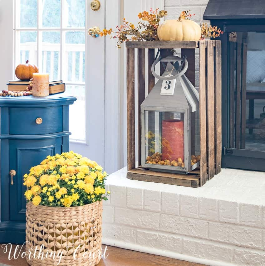 Place a lantern in a wood crate, topped with an artificial pumpkin and foliage for a super fast and easy display for your fireplace || Worthing Court