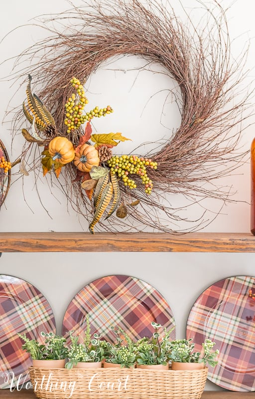 Make a super easy fall wreath by tucking a couple of faux floral bushes in between the stems of the wreath. Done in 5 minutes! || Worthing Court #falldecor #fallwreath