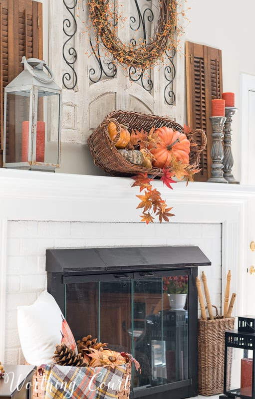 A rustic basket filled with faux pumpkins and faux fall leaves || Worthing Court #falldecor #rustic #mantel