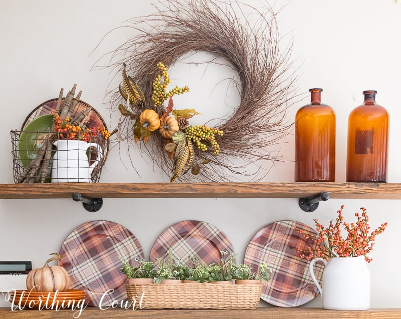 Rustic farmhouse open shelves decorated for fall with plaid plates, brown glass bottles and a grapevine wreath || Worthing Court #falldeco #fallwreath #plaid