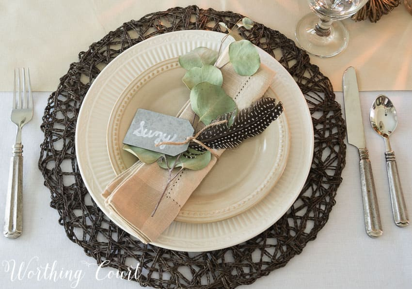 place setting with brown placemat, white dishes and neutral linen napkin