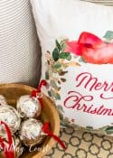 Merry Christmas pillow beside wood bowl filled with silver bells