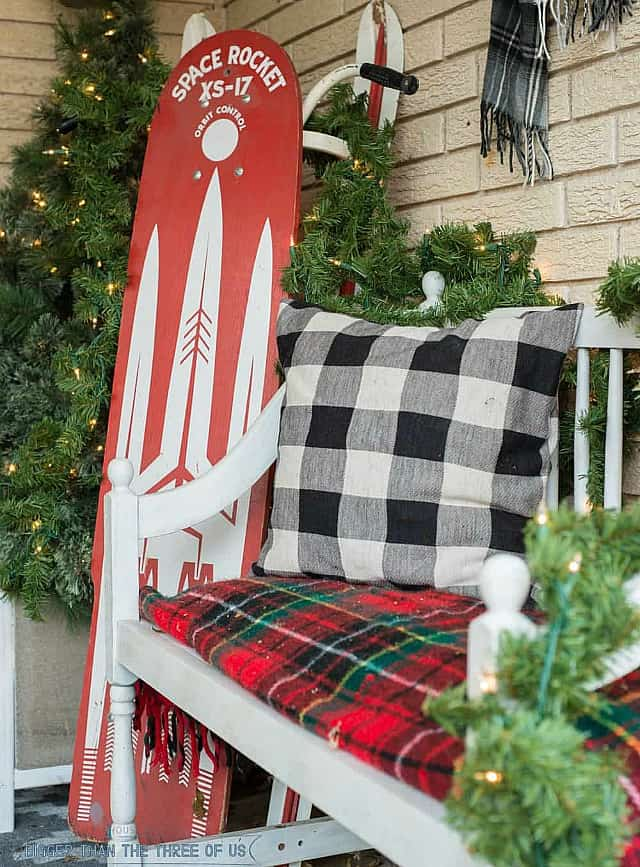 A small bench with a buffalo checked pillow is on the porch.