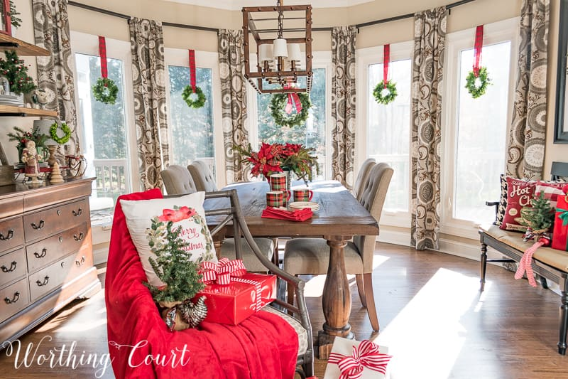Christmas wreaths suspended with plaid ribbon in a bay window #christmas #christmasdecor #christmaswreath #tartanplaid