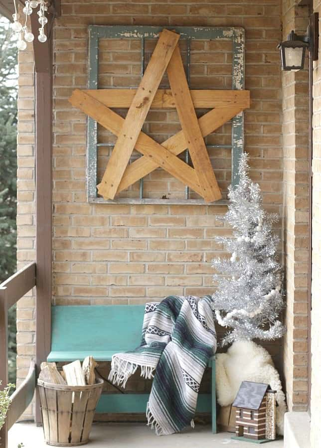 A wooden star in a picture frame is above a sitting bench on the porch.