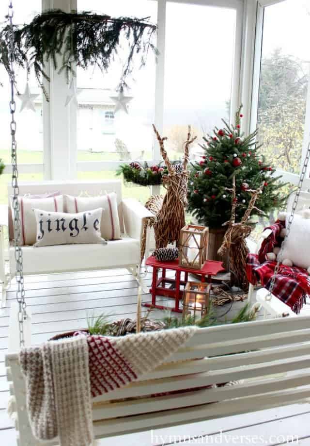 Twig deers, a small swing bench and a small Christmas tree is on the white porch.
