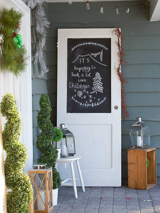 There is a white door with chalkboard beside the front door on the porch.