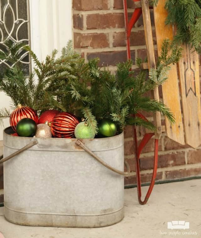 A galvanized bucket is filled with ornaments and evergreen branches on the porch.