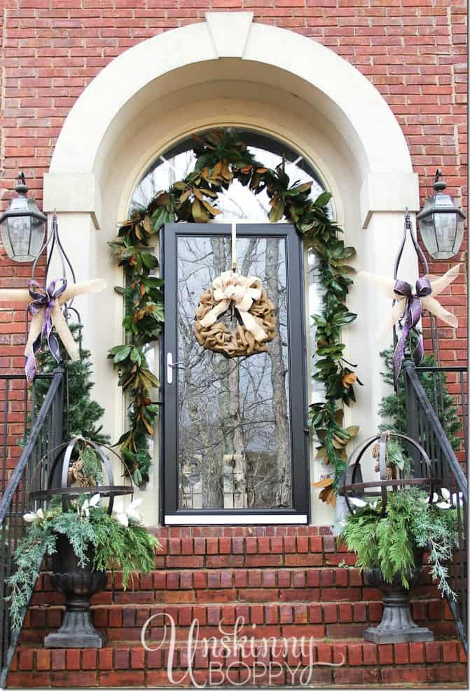 The front stoop decorated with holly and ivy on the porch.
