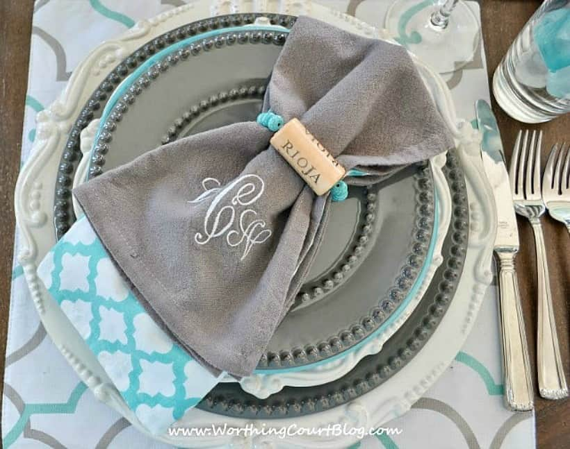 place setting with gray and white dishes and diy wine cork napkin rings