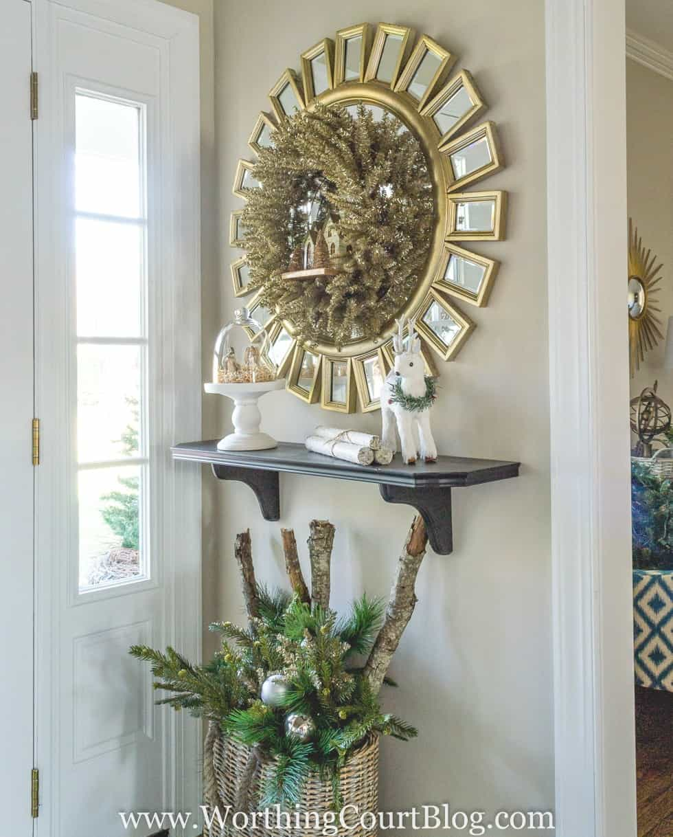 Rustic glam Christmas foyer decorations with a gold sunburst mirror and a small wreath on it.