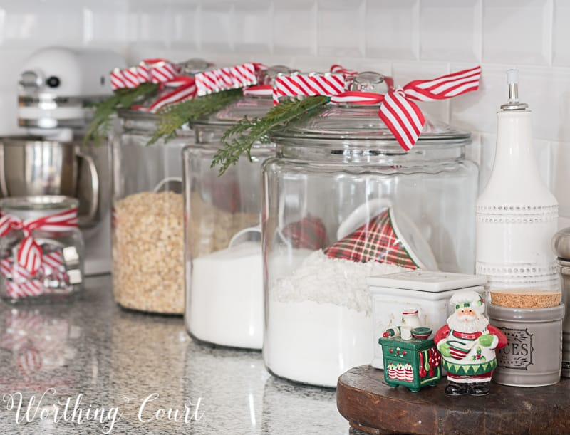 Glass kitchen canisters with faux greenery and Christmas ribbon #christmasdecor