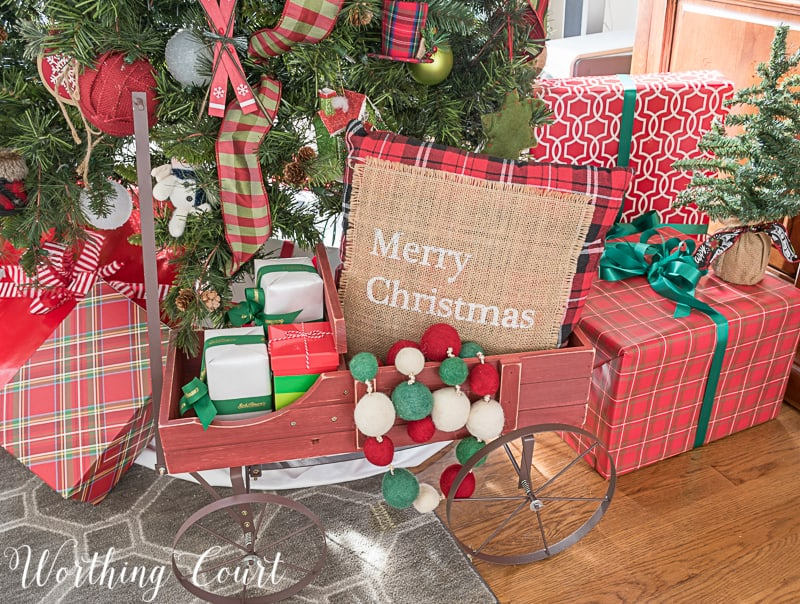 Small wagon under a Christmas tree makes a cute holder for wrapped gifts #Christmasdecor