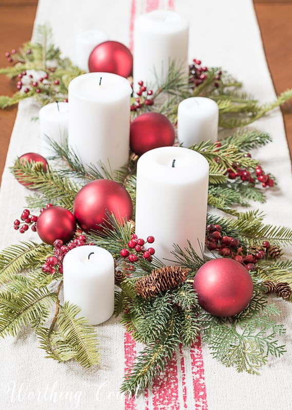 Christmas centerpiece with faux greenery, white candles, red berries and red Christmas tree ornaments #christmasdecor #centerpiece