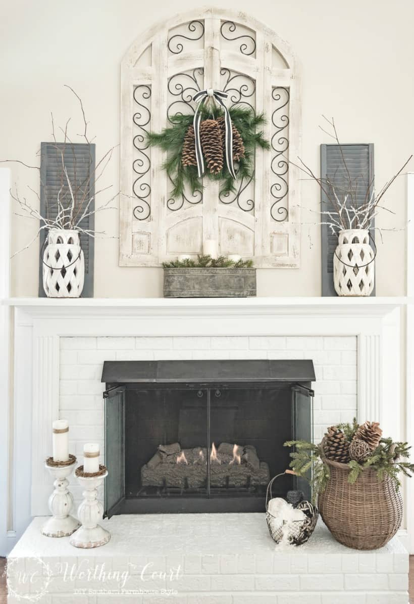 Fireplace decorated for winter with a wicker basket in front of the fireplace.