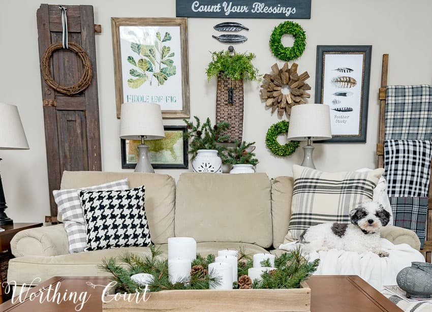 The living room with a neutral couch and throw pillows on the couch, a candle display on the coffee table and wreaths on the wall.