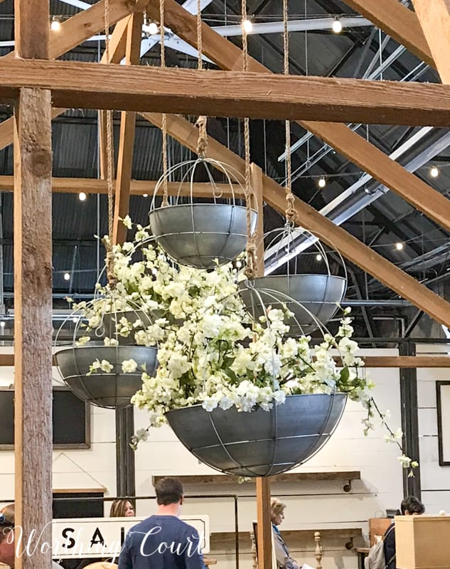 Hanging metal baskets filled with flowers at Magnolia Market #fixerupper #magnoliamarket #flowers #springdecoratingideas #summerdecoratingideas