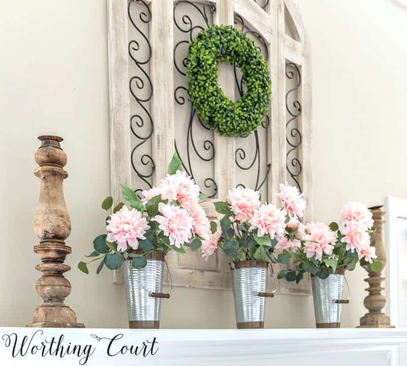 trio of pink peonies on a fireplace mantel
