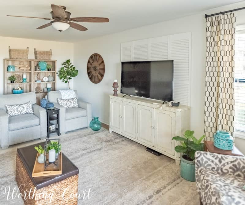 A Living Room Makeover Created With Summer In Mind - Before And After Room Reveal! Mount bi-fold doors behind a large tv to help fill the wall. #decoratearoundatv#summerdecor #summerdecoratingideas #livingroomdecor #familyroomdecor #modernfarmhousedecoratingideas #WorthingCourtBlog # #neutraldecoratingideas coastaldecoratingideas