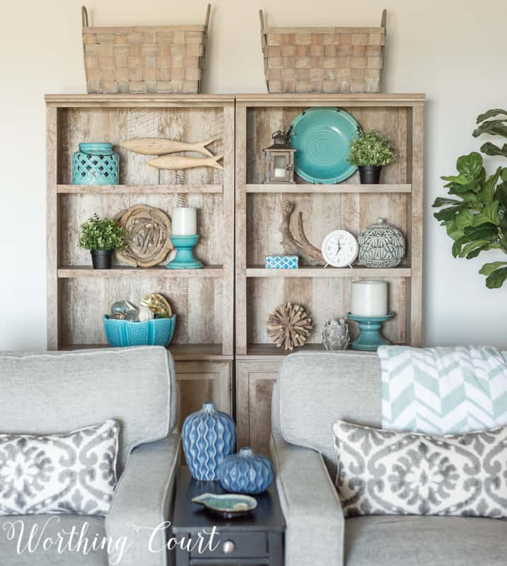 A Living Room Makeover Created With Summer In Mind - Before And After Room Reveal! Driftwood finish bookcases with coastal decor. #summerdecor #summerdecoratingideas #livingroomdecor #familyroomdecor #modernfarmhousedecoratingideas #WorthingCourtBlog # #neutraldecoratingideas coastaldecoratingideas #bookcasedecor