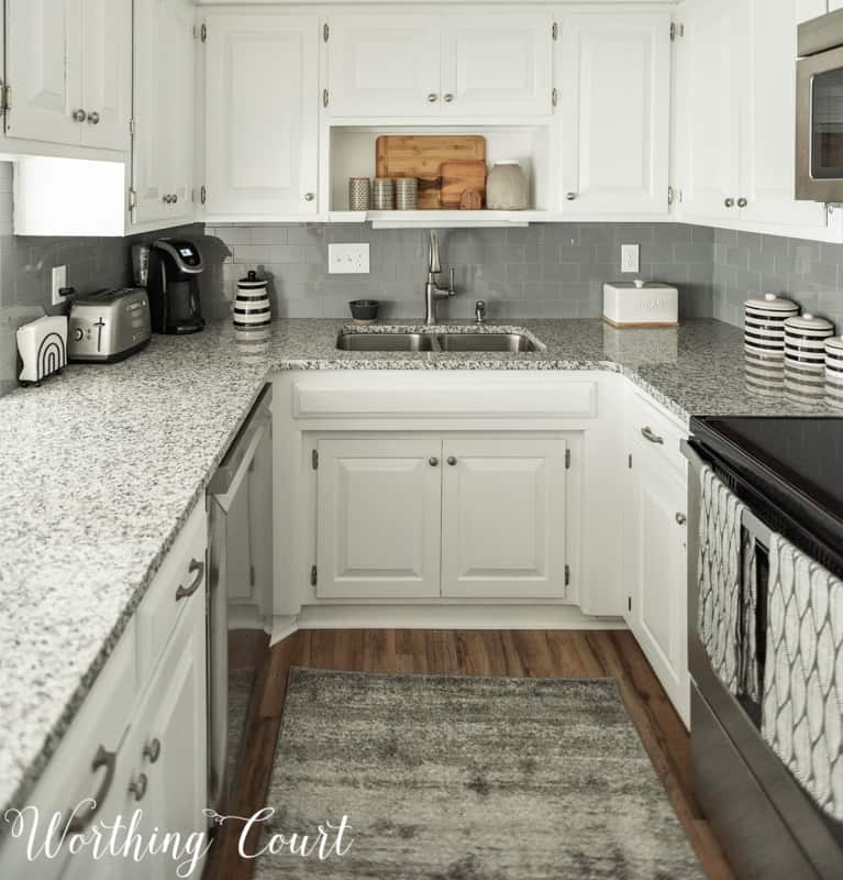 How To Make A Kitchen Look Brand New Without A Remodel. Small white kitchen with gray glass subway tile backsplash and luna white granite counters with stainless steel appliances. #whitekitchen #kitchenideas #kitchenideas #smallkitchen #farmhousekitchen #kitchendesign #kitchendecor #modernfarmhousekitchen #smallkitchen #kitchencounters #kitchenbacksplash