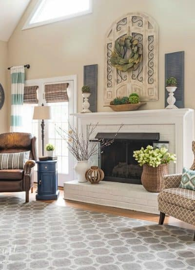 Oversized wood art above a fireplace in a room with a vaulted ceiling. #farmhousestyle #paintedfireplace #brickfireplace #fireplacmakeover #manteldecoratingideas #springdecor