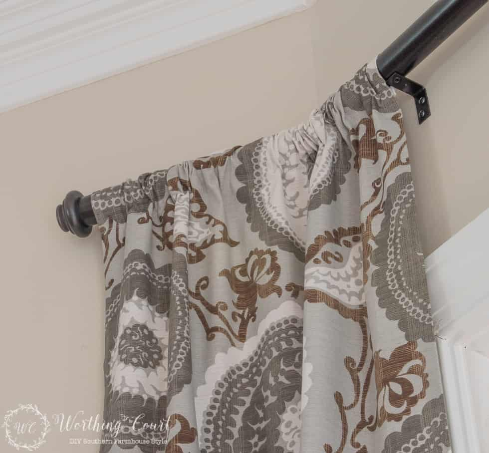 gray print draperies on a diy pvc pipe curtain rod in a bay window