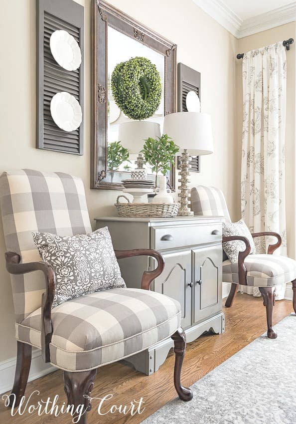 Farmhouse dining room with Martha Washington side chairs upholstered with buffalo check fabric and gray accent chest. #diningroomdecoratingideas #farmhousedecor #buffalocheck #neutralcolors