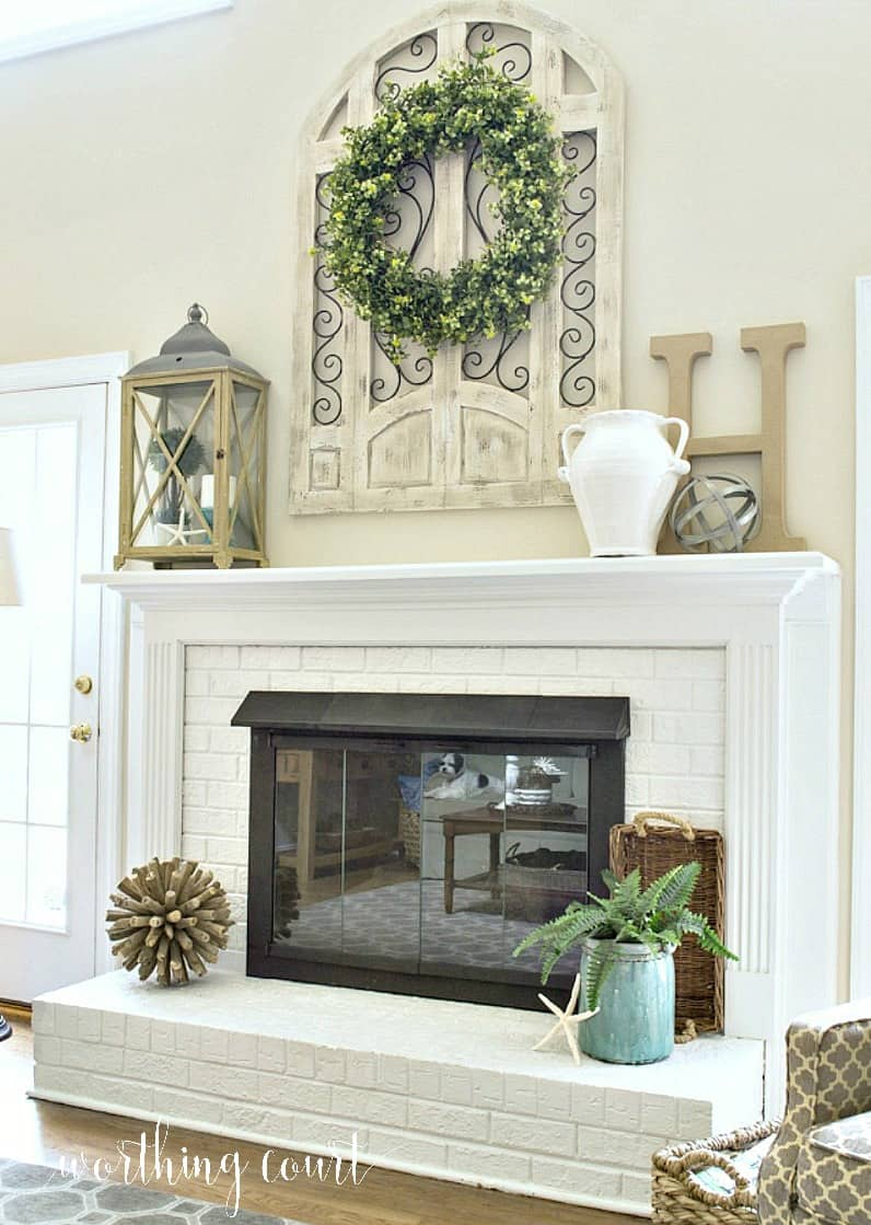 Red brick fireplace with oak surround and mantel painted white and brass fireplace screen painted with high temp spray paint. Tall ceilings with arch window wall decor above mantel. #farmhousedecor #makeover #diy #paintedfireplace #manteldecor #fireplacedecor #paintedbrick