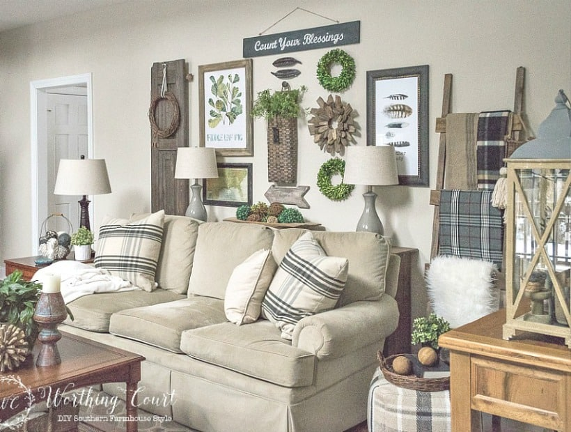 Family room sofa with rustic farmhouse gallery wall in neutral colors with touches of artificial greenery. #familyroomdecor #livingroomdecor #farmhousedecor #gallerywall #decoratingideas #vintagedecor