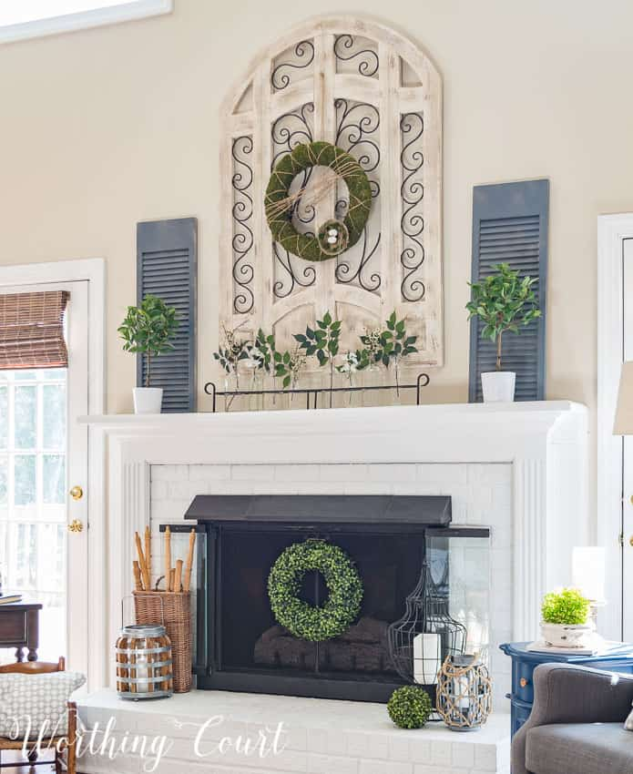 Red brick fireplace and oak mantel and surround painted white, brass firescreen painted with high temp black spray paint, large wood and metal arch window wall decor, spring fireplace decor