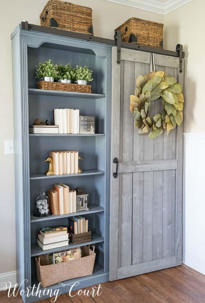 A diy hack turning an old set of cherry bookcases into farmhouse style bookcases with paint and the addition of a sliding barn door. #upcyclingideas #repurposedfurniture #repurpose #upcycledfurniture #upcycledideas