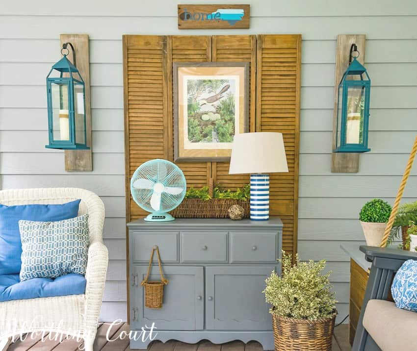 Bifold shutter doors, flanked by hanging lanterns, use as a backdrop to a vintage chest on a screen porch. #screenporch #vintagefurniture #farmhousestyle