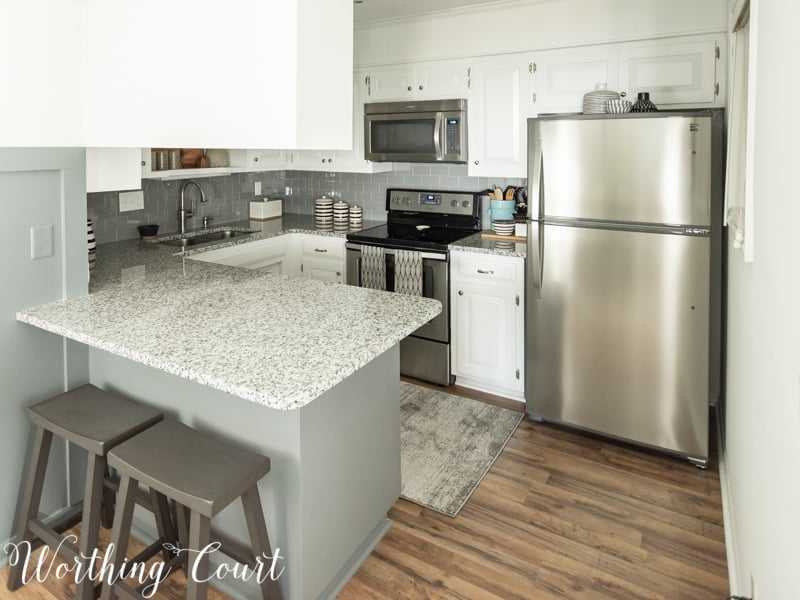 Small galley kitchen makeover with painted white cabinets, diy glass tile backsplash, stainless appliances, new flooring and new granite counters #kitchenmakeover #galleykitchen #whitecabinets #diybacksplash